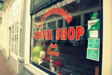 In Amsterdam, a coffee shop is a place where you can legally buy soft drugs (marijuana or hashish) as well as coffee and tea. A coffee house is strictly an establishment for refreshments, no drugs.